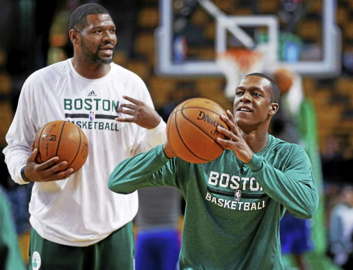 Celtics guard Rajon Rondo, right, shoots during pregame warm-ups as assistant coach Walter McCarty watches prior to a Dec. 11, 2013 game in Boston.