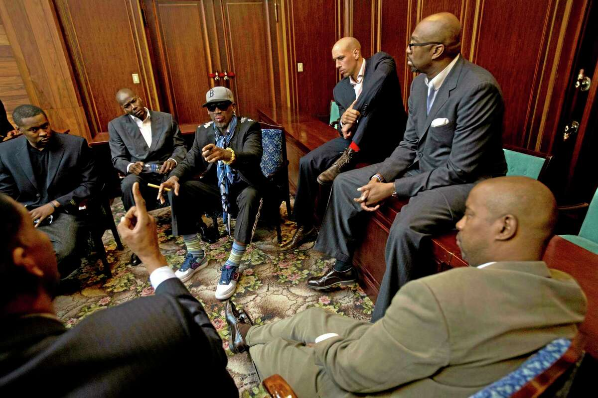 Dennis Rodman speaks with fellow US basketball players during a team meeting at a Pyongyang, North Korea hotel Tuesday, Jan. 7, 2014. Rodman came to the North Korean capital with a team of USA basketball stars for an exhibition game on Jan. 8, the birthday of North Korean leader Kim Jong Un. Clockwise from bottom left are Charles D. Smith, unidentified, Cliff Robinson, Rodman, Doug Christie, Vin Baker, and unidentified. (AP Photo/David Guttenfelder)
