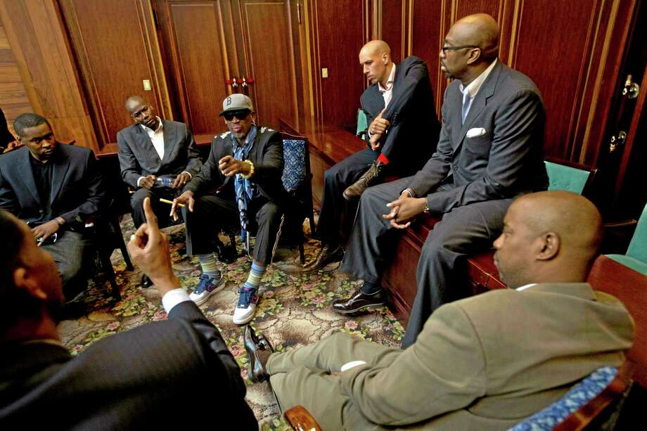 Dennis Rodman speaks with fellow US basketball players during a team meeting at a Pyongyang, North Korea hotel Tuesday, Jan. 7, 2014. Rodman came to the North Korean capital with a team of USA basketball stars for an exhibition game on Jan. 8, the birthday of North Korean leader Kim Jong Un. Clockwise from bottom left are Charles D. Smith, unidentified, Cliff Robinson, Rodman, Doug Christie, Vin Baker, and unidentified. (AP Photo/David Guttenfelder) Photo: AP / AP