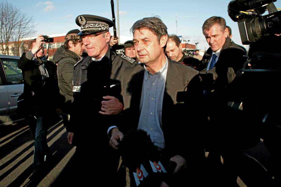 Goodyear's human resources chief, Bernard Glesser, center, and the firm's production manager Michel Dheilly, center right, leave the Goodyear plant in Amiens, northern France, Tuesday, Jan. 7, 2014. Two Goodyear managers held captive by angry French workers were freed Tuesday after police intervened, ending two days of standoff over the factoryís bleak future. The release outraged union members, who made a bonfire of tires in front of the plant. It also left unresolved the larger problems that have dogged the plant in Amiens in northern France, which Goodyear has tried to sell or shutter for five years.  (AP Photo/Thibault Camus) Photo: AP / AP