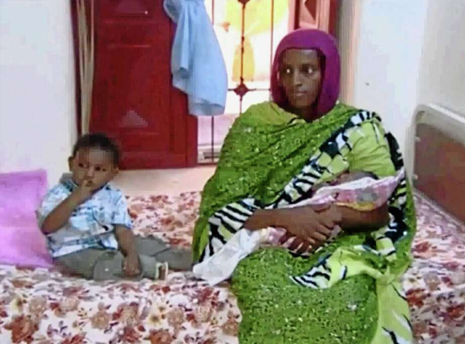 FILE - In this file image made from an undated video provided Thursday, June 5, 2014, by Al Fajer, a Sudanese nongovernmental organization, Meriam Ibrahim, sitting next to Martin, her 18-month-old son, holds her newborn baby girl that she gave birth to in jail last week, as the NGO visits her in a room at a prison in Khartoum, Sudan. Sudan's official news agency, SUNA, said the Court of Cassation in Khartoum on Monday, June 23, canceled the death sentence against 27-year-old Meriam Ibrahim after defense lawyers presented their case. The court ordered her release. (AP Photo/Al Fajer, File) Photo: AP / Al Fajer