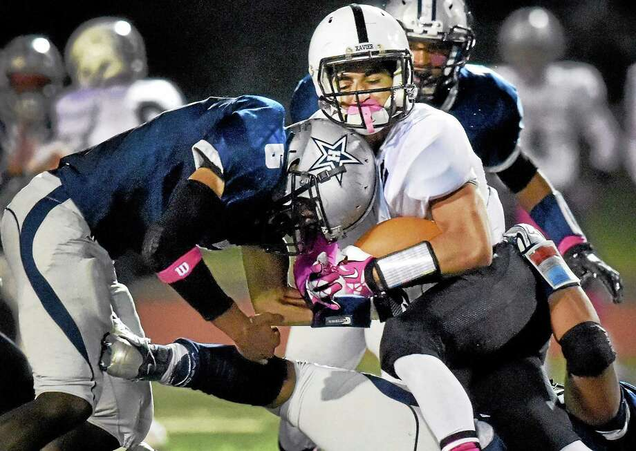 (Peter Hvizdak - New Haven Register) Tyler Williams of Hillhouse High School, left,  puts a hit on Teddy Duarte of Xavier during second quarter football action at  Southern Connecticut State University Friday evening, October 3, 2014. Photo: ©2014 Peter Hvizdak / ©2014 Peter Hvizdak