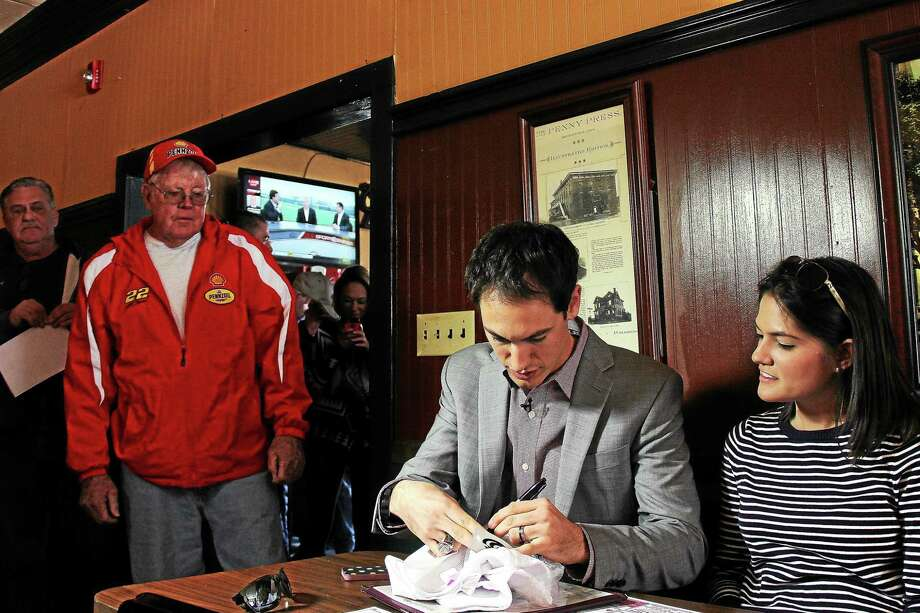 Longtime family friend Wayne Duff watches Joey Logano sign his name to a shirt at Portland Restaurant. Logano came to town on Tuesday with his new wife, Brittany. Photo: Kathleen Schassler — The Middletown Press  / Kathleen Schassler All Rights
