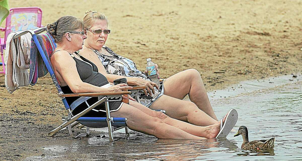 Two sunbathers keep cool at Sears Park at Lake Pocotopaug in this archive photograph. Officials have asked police to step up patrols of the park after multiple reports of rule-breaking and inappropriate activity.