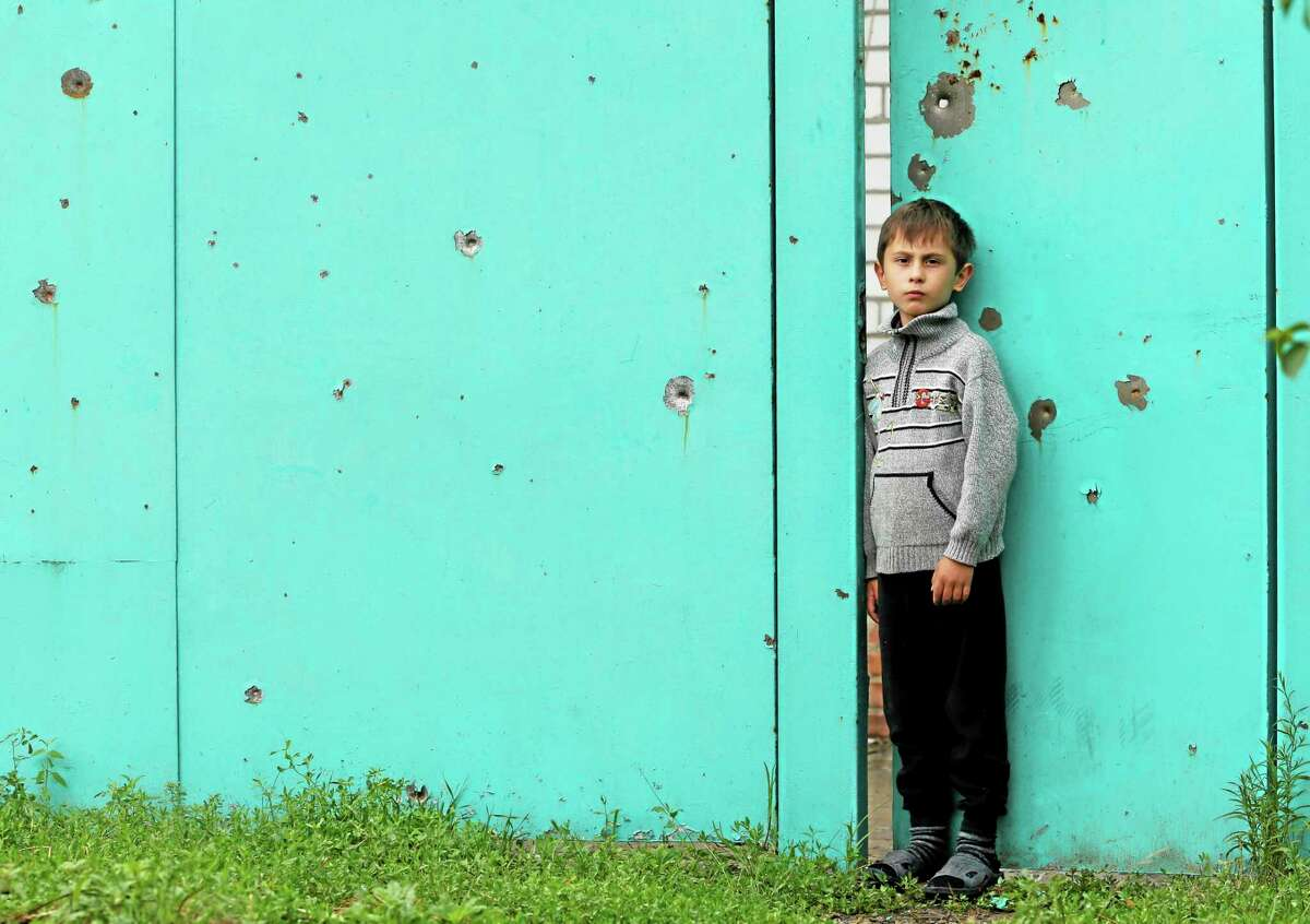 Vadim, 9, stands at a damaged gate of his house, Wednesday, June 25, 2014, after it was hit during a mortar attack from Ukrainian government forces Monday, June 23, in Slovyansk, Donetsk region, eastern Ukraine. Residential areas came under mortar shelling on Monday, from government forces. (AP Photo/Dmitry Lovetsky)