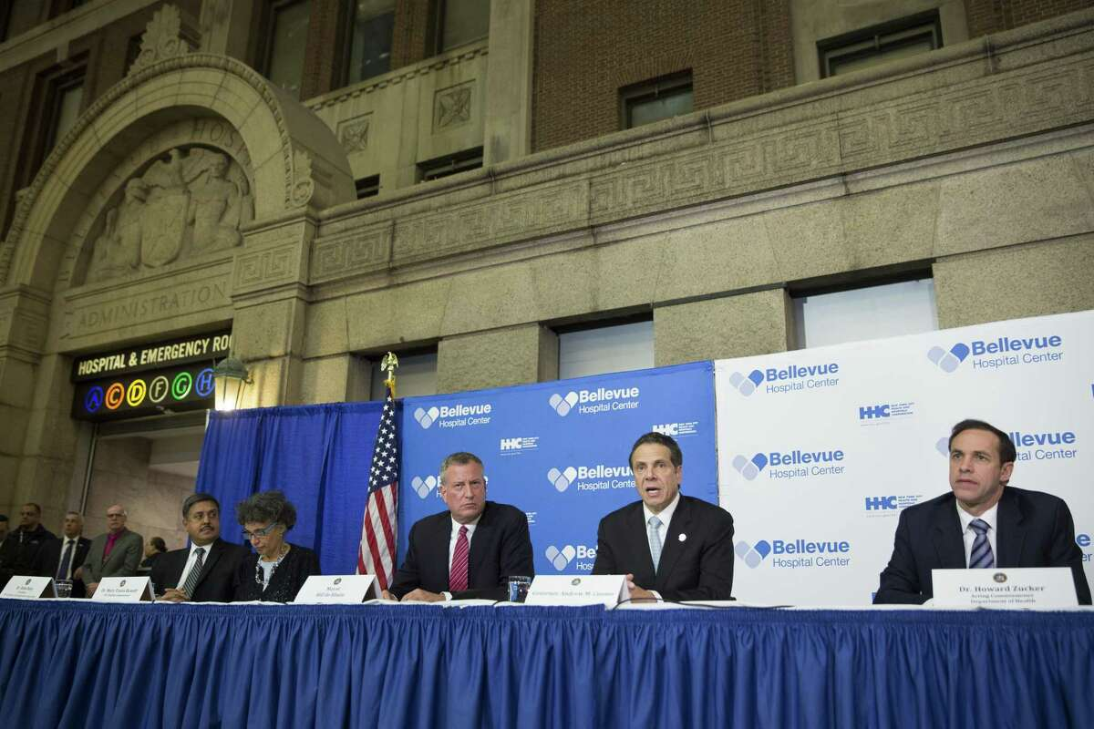 New York Gov. Andrew Coumo, center right, speaks during a news conference alongside New York City Mayor Bill de Blasio, center left, at Bellevue Hospital to discuss Craig Spencer, a Doctors Without Borders physician who tested positive for the Ebola virus, Thursday, Oct. 23, 2014, in New York. Spencer recently returned to the city after treating Ebola patients in West Africa. (AP Photo/John Minchillo)