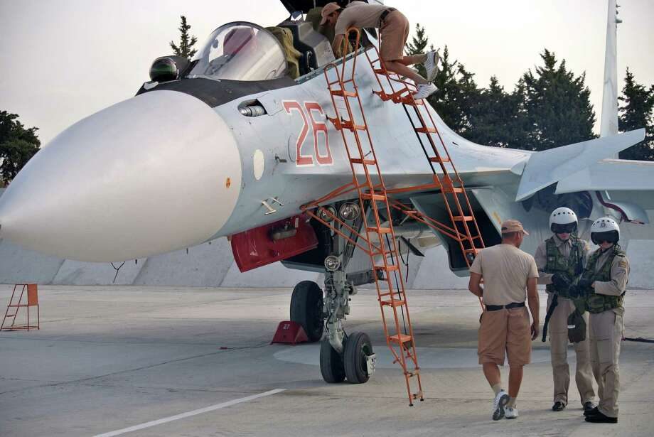 Russian air force crew stand next to a fighter jet in preparation for a combat mission at Hemeimeem airbase, Syria,  Thursday, Oct. 22, 2015. Since early morning, Russian combat jets have been taking off from this base in western Syria, heading for missions. (AP Photo/Vladimir Isachenkov) Photo: AP / AP