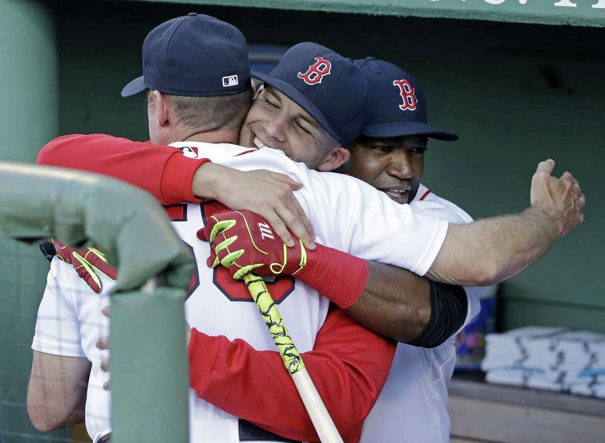 Boston Red Sox designated hitter David Ortiz, far right, starting pitcher Justin Masterson, middle, and third base coach Brian Butterfield, left, share a group hug in the dugout prior to a baseball game against the Baltimore Orioles at Fenway Park Wednesday, June 24, 2015, in Boston.