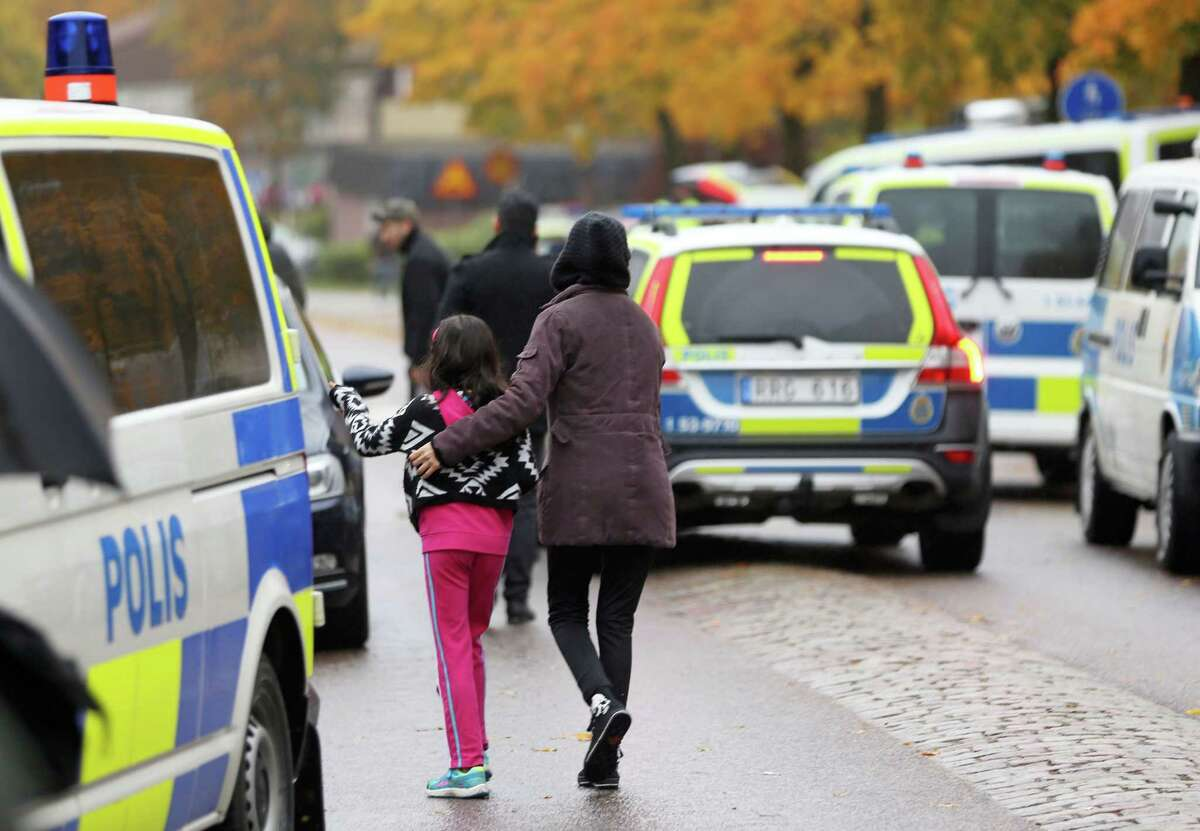 Students and parents leave near the scene of a sword attack by a masked man at the Kronan school in Trollhattan, Sweden on Oct. 22, 2015. At least six people were injured, and the offender was shot by the police.