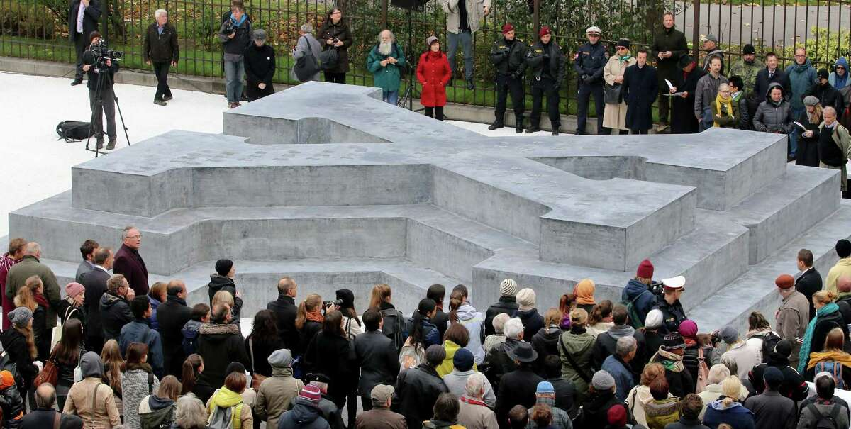 People surround a memorial dedicated to deserters of the Nazi Wehrmacht troops and victims of their military justice during its unveiling ceremony in downtown Vienna, Austria, Friday, Oct. 24, 2014. The memorial is located in front of the presidential office in the Hofburg palace and the federal chancellery. (AP Photo/Ronald Zak)