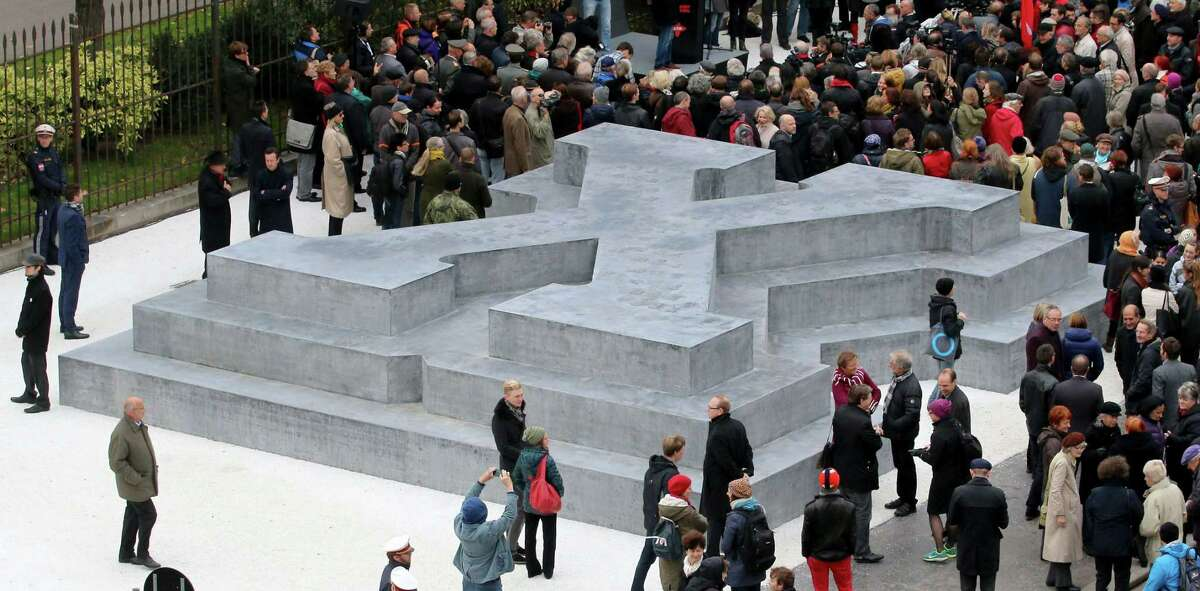 People surround a memorial dedicated to deserters of the Nazi Wehrmacht troops and victims of their military justice during its unveiling ceremony in downtown Vienna, Austria, Friday, Oct. 24, 2014. The memorial is located in front of the presidential office in the Hofburg palace and the federal chancellery, background. (AP Photo/Ronald Zak)