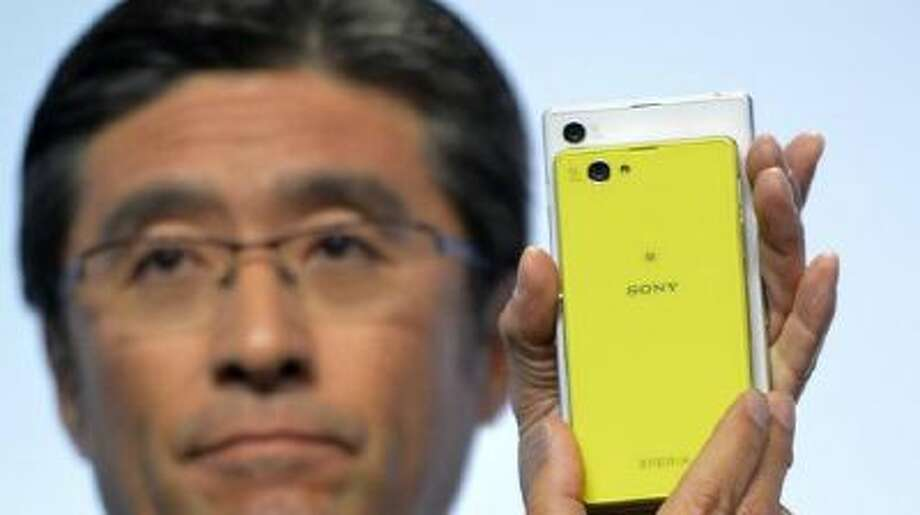 Kunimasa Suzuki, executive vice president of Sony Corporation and president and chief executive officer of Sony Mobile Communications, unveils the new Sony EXPERIA Z1 Compact during the Sony news conference at the International Consumer Electronics Show Monday, Jan. 6, 2014, in Las Vegas.