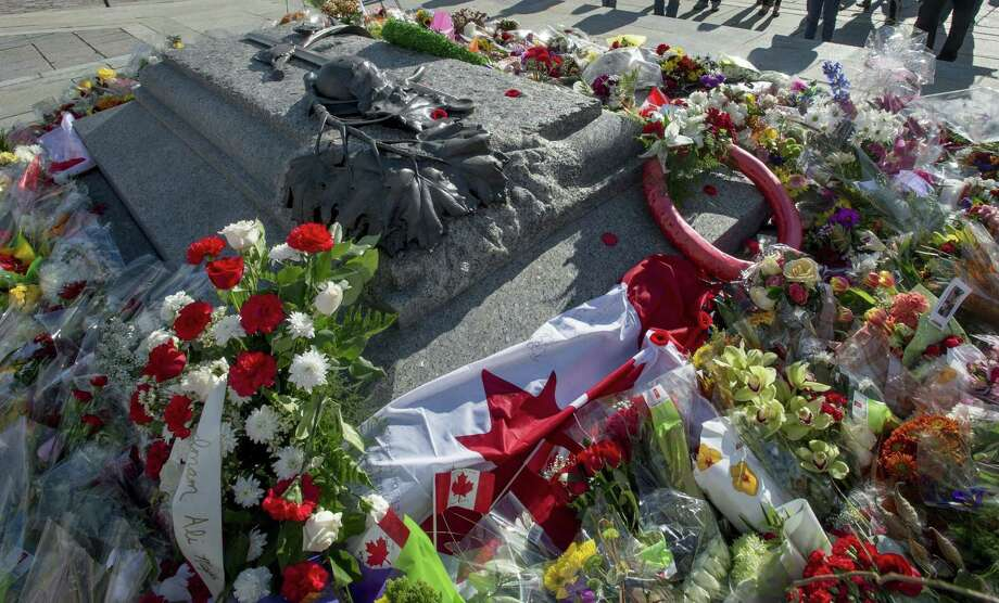 Flowers and flags over a memorial at the Tomb of the Unknown Soldier is pictured at the National War Memorial, in Ottawa on Friday, Oct. 24, 2014.  Canadians are mourning the loss of Cpl. Nathan Cirillo, the army reservist who was shot dead as he stood guard before the Tomb of the Unknown soldier on Wednesday.  (AP Photo/The Canadian Press, Justin Tang) Photo: AP / The Canadian Press