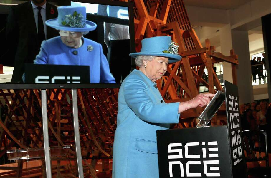 Britain's Queen Elizabeth II sends the first royal tweet under her own name to declare the opening of the new Information Age Galleries at the Science Museum, South Kensington, London, Friday Oct. 24, 2014. Normally a plaque is unveiled to herald the launch of a new project, but after touring the attraction dedicated to the history of communication and information the Queen touched a tablet screen to send her message to the world. (AP Photo/PA, Chris Jackson)  UNITED KINGDOM OUT  NO SALES  NO ARCHIVE Photo: AP / PA