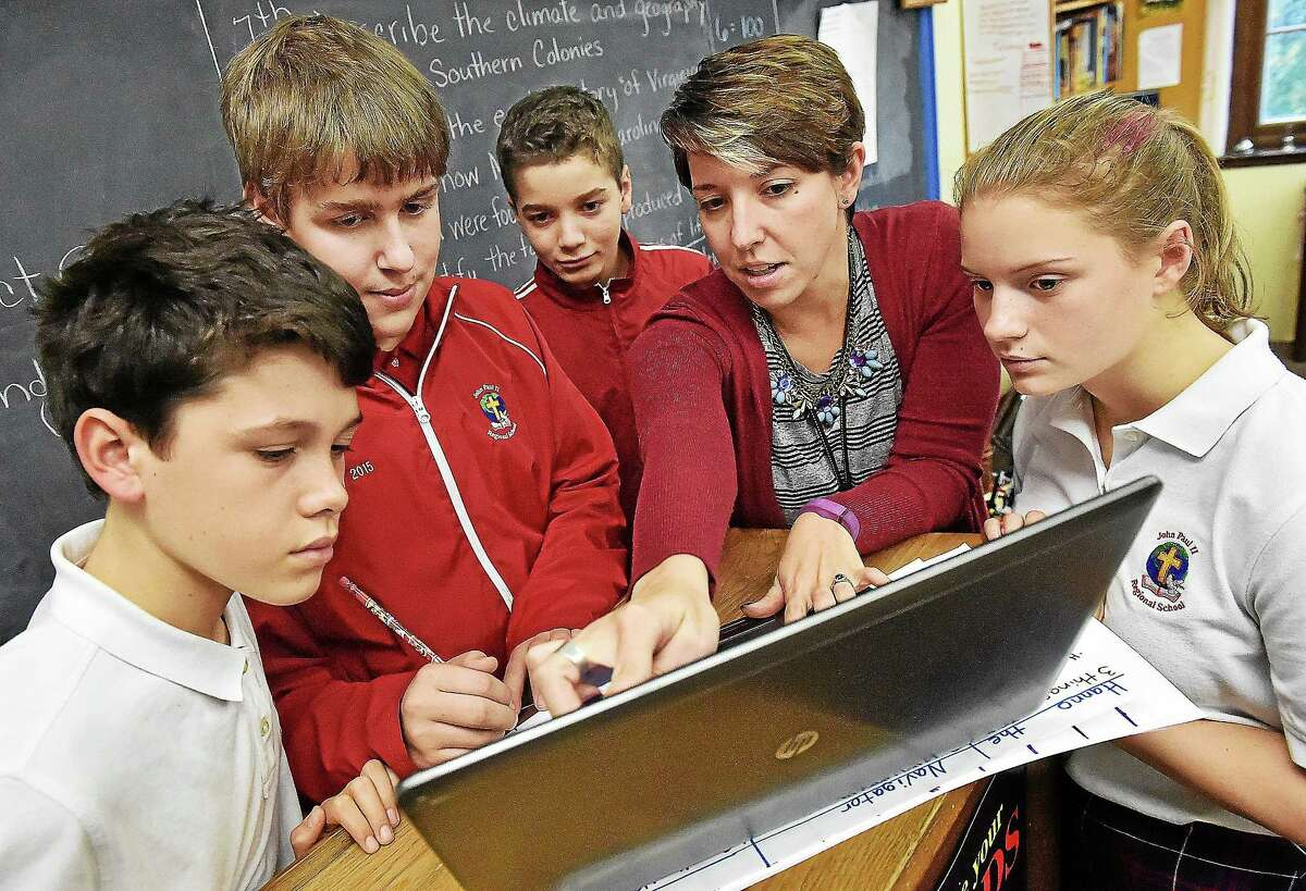From left, members of St. John Paull II robotics team Eduardo Basauri, Cody Eckstrom, EJ Leary, math teacher and robotics coach Erin Vogel and Linda Brown watch a YouTube video of the First Lego League Challenge Oct. 22. The team, JPII Roar, is in its inaugeral season and planning robot strategies for its first competition Nov. 13 at Old Lyme High School.