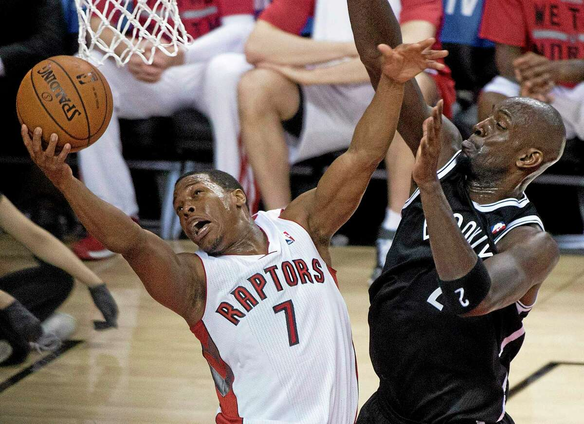 In this May 4 file photo, Toronto Raptors guard Kyle Lowry, left, gets fouled by Brooklyn Nets forward Kevin Garnett.