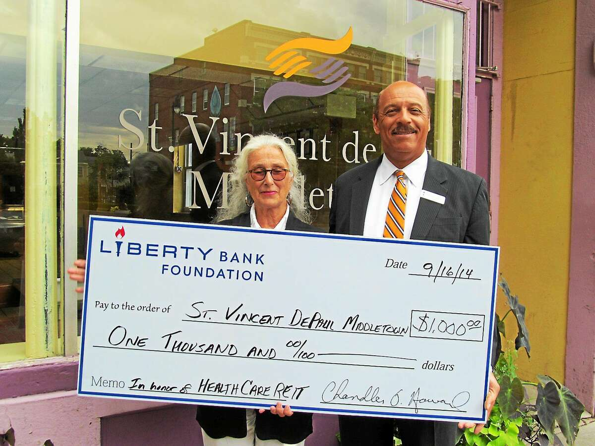 Lydia Brewster, St. Vincent de Paul's assistant director for Community Services, and Chandler Howard, Liberty Bank president/CEO, celebrated with guests outside of the SVD Soup Kitchen recently after receiving a gift from a very grateful company that was spared being a victim of identity theft.