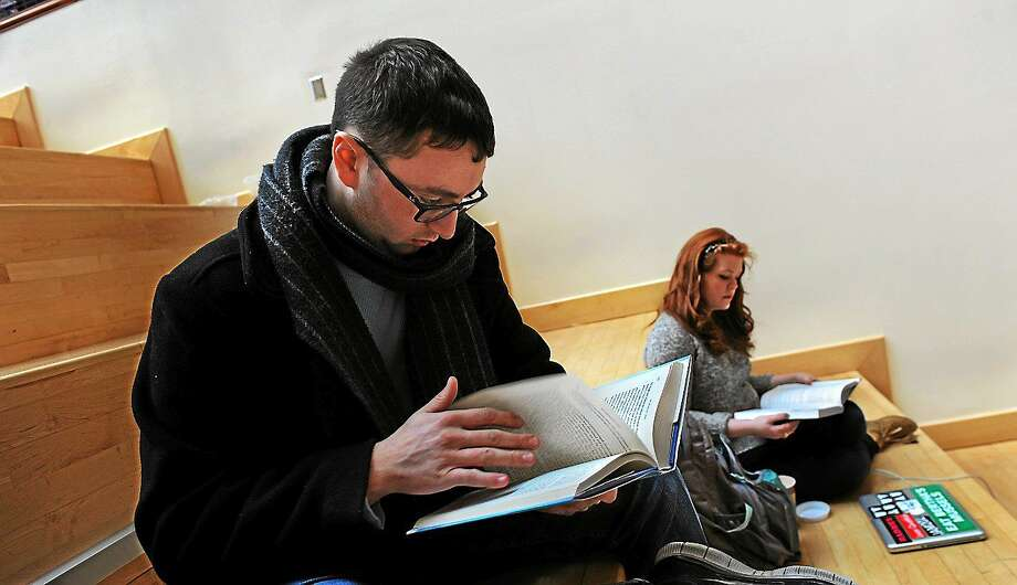Frank Schembari, 20, says that he loves the feel of a book in his hands. At right is another fan of the printed word, Wallis Neff, 19. They are in the atrium of American University's School of International Service in Washington, D.C. Photo: Washington Post Photo/Michael S. Williamson