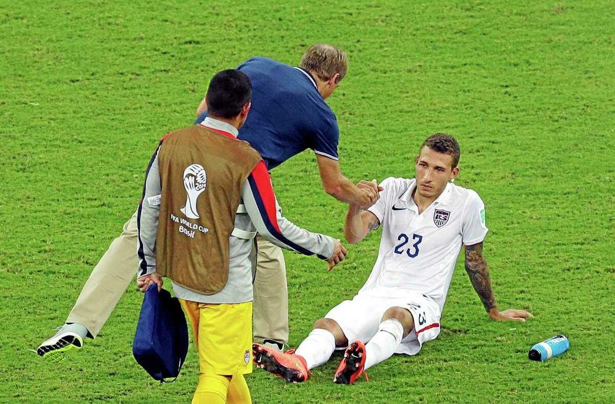 The United States' Fabian Johnson, right, shakes hands with coach Jurgen Klinsmann after a 2-2 draw in the group G World Cup match against Portugal on Sunday at the Arena da Amazonia in Manaus, Brazil.
