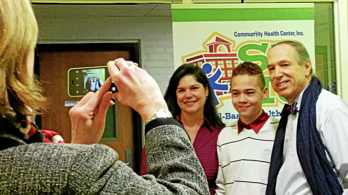 Student advocate Onix Rivera, center, with state Sen. Dante Bartolomeo, left, and Mark Masselli, president and chief executive officer of the Community Health Center, have their photo taken by School Superintendent Patricia Charles.