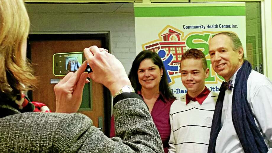 Student advocate Onix Rivera, center, with state Sen. Dante Bartolomeo, left, and Mark Masselli, president and chief executive officer of the Community Health Center, have their photo taken by School Superintendent Patricia Charles. Photo: Kathleen Schassler — The Middletown Press