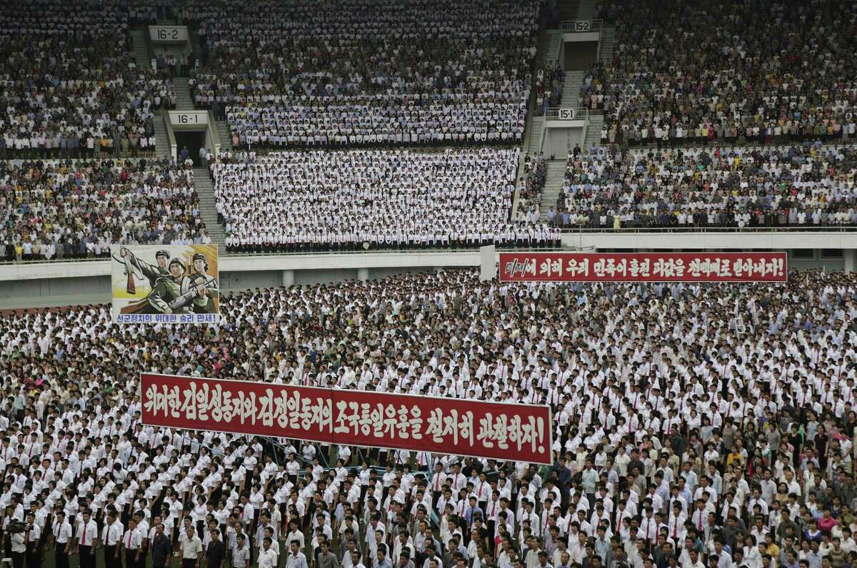 """North Koreans gather at the """"Pyongyang Mass Rally on the Day of the Struggle Against the U.S."""" to mark the 65th anniversary of the outbreak of the Korean War at the Kim Il Sung stadium, Thursday, June 25, 2015, in Pyongyang, North Korea. The month of June in North Korea is known as the """"Struggle Against U.S. Imperialism Month"""" and it's a time for North Koreans to swarm to war museums, mobilize for gatherings denouncing the evils of the United States and join in a general, nationwide whipping up of the anti-American sentiment. The banner at the bottom reads: """"Let's completely carry out great comrades Kim Il Sung and Kim Jong Il's dying wishes of national unification!"""" and the banner on the top reads: """"Let's retaliate American imperialists by 1,000 times for the blood spilled by our nation!"""" (AP Photo/Wong Maye-E)"""