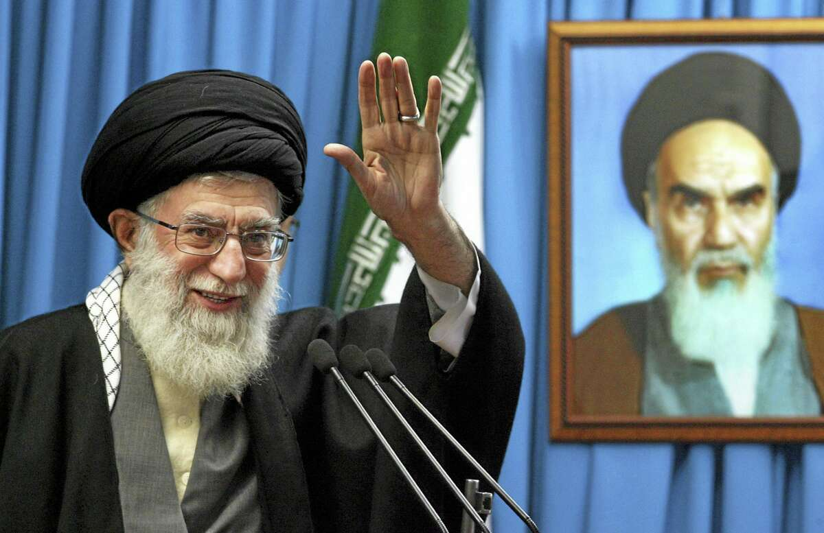 In this archived photo, Iranian supreme leader Ayatollah Ali Khamenei waves to the worshippers, in front of a portrait of the late revolutionary founder Ayatollah Khomeini, before he delivers his Friday prayers sermon at the Tehran University campus, Iran.