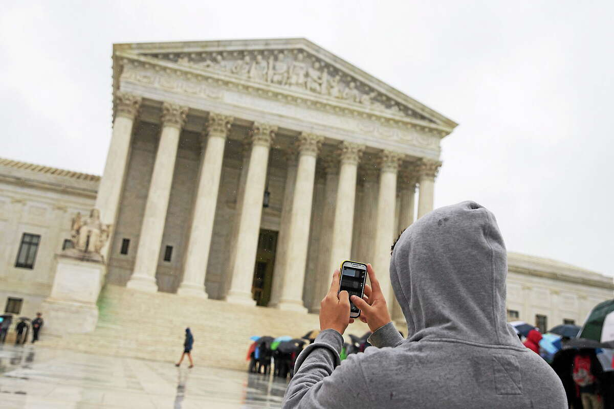This April 29, 2014 photo shows a visitor to the Supreme Court uses his cellphone to take a photo of the court in Washington. A unanimous Supreme Court says police may not generally search the cellphones of people they arrest without first getting search warrants.
