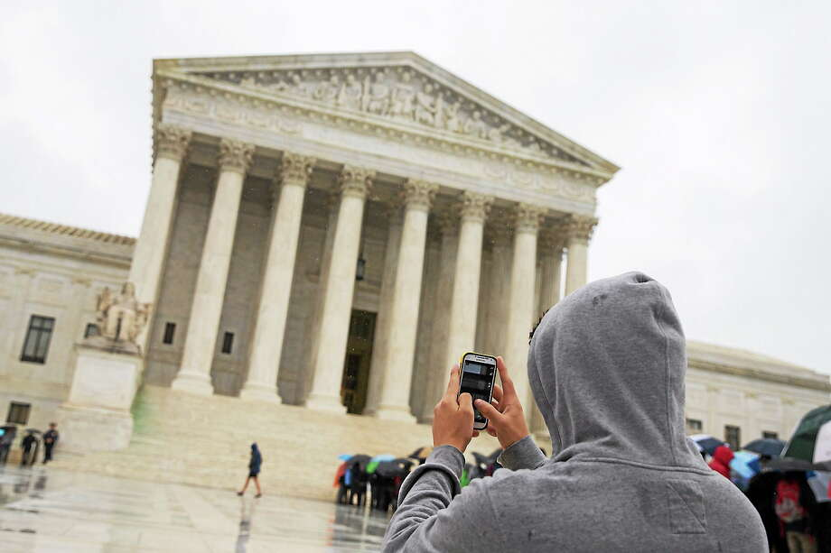 This April 29, 2014 photo shows a visitor to the Supreme Court uses his cellphone to take a photo of the court in Washington. A unanimous Supreme Court says police may not generally search the cellphones of people they arrest without first getting search warrants. Photo: AP Photo, File  / AP