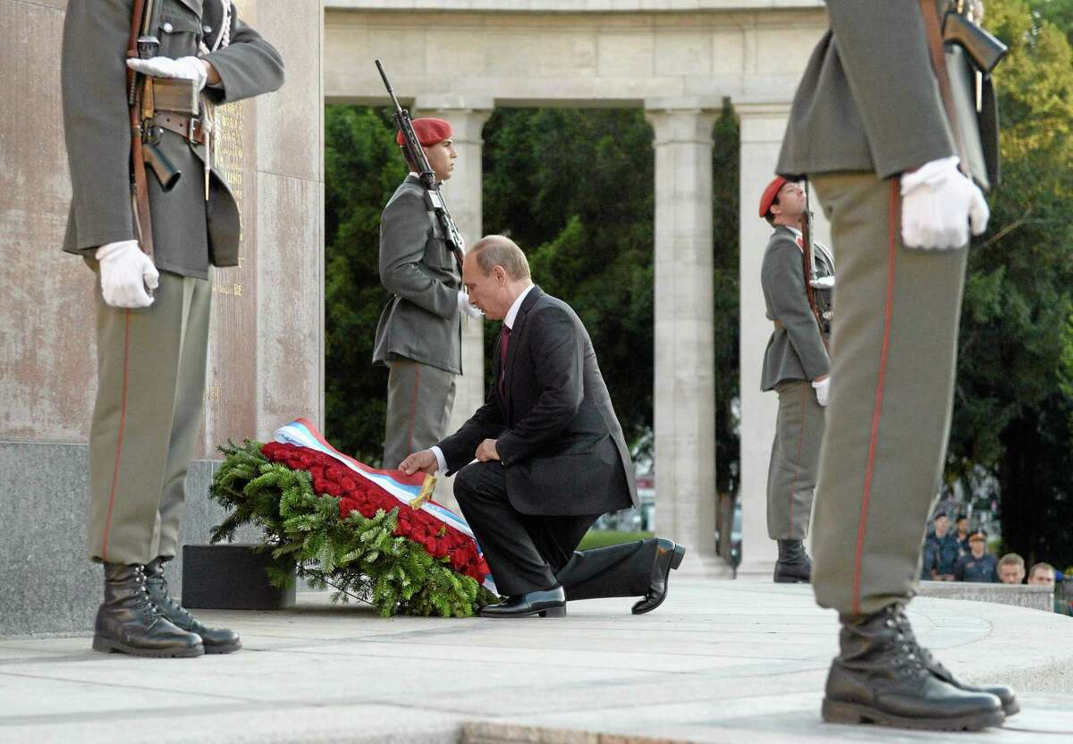 In this Tuesday, June 24, 2014 photo, Russia's President Vladimir Putin adjusts a ribbon during a wreath laying ceremony at a monument to Soviet soldiers, who died in WWII, on Schwarzenbergplatz Square in Vienna, Austria. (AP Photo/RIA Novosti, Alexei Nikolsky, Presidential Press Service)