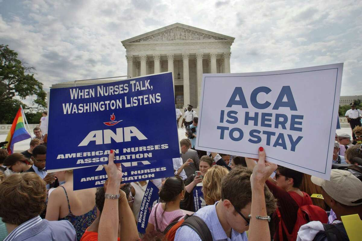 Supporters of the Affordable Care Act hold up signs as the opinion for health care is reported outside of the Supreme Court in Washington Thursday.