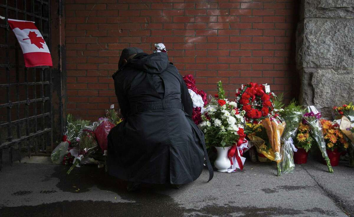 A man places flowers at a memorial outside the gates of the John Weir Foote Armory, the home of the Argyll and Sutherland Highlanders of Canada in Hamilton, Ontario, Wednesday, Oct. 22, 2014, in memory of Canadian soldier Nathan Cirillo. Witnesses say Cirillo, posted at the National War Memorial near Parliament Hill in Ottawa, was gunned down at point-blank range Wednesday morning by a man carrying a rifle and dressed all in black, his face half-covered. (AP Photo/The Canadian Press, Aaron Lynett)