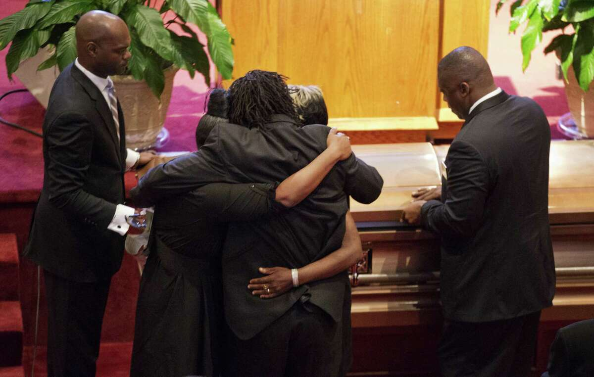 Family members embrace as the casket for Ethel Lance is closed during her funeral service at Emanuel AME Church, Thursday, June 25, 2015, in North Charleston, S.C. Lance was one of the nine people killed in the shooting at Emanuel AME Church last week in Charleston.