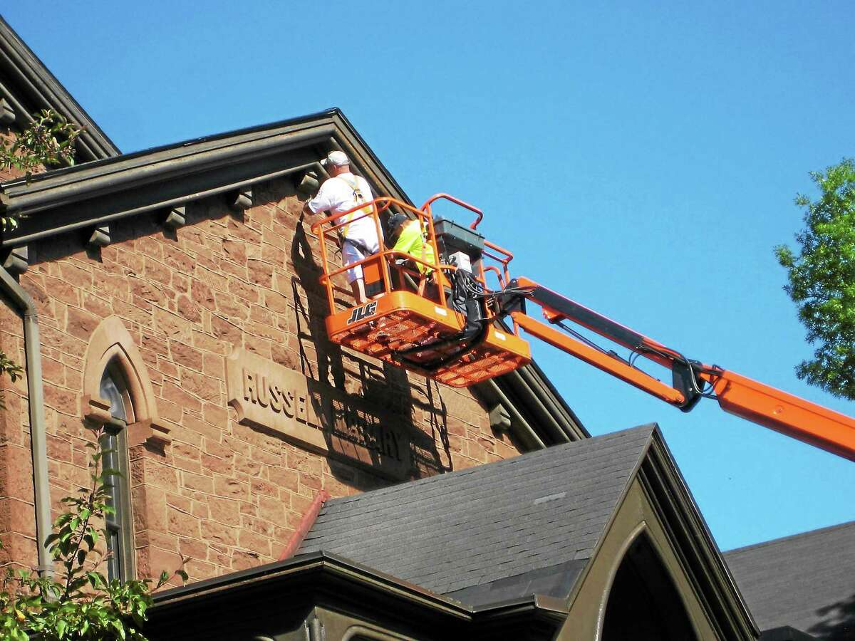 Submitted photo High in the air, workers scrape and paint the front of Russell Library in Middletown as the 180-year-old building and its additions undergo exterior renovation.
