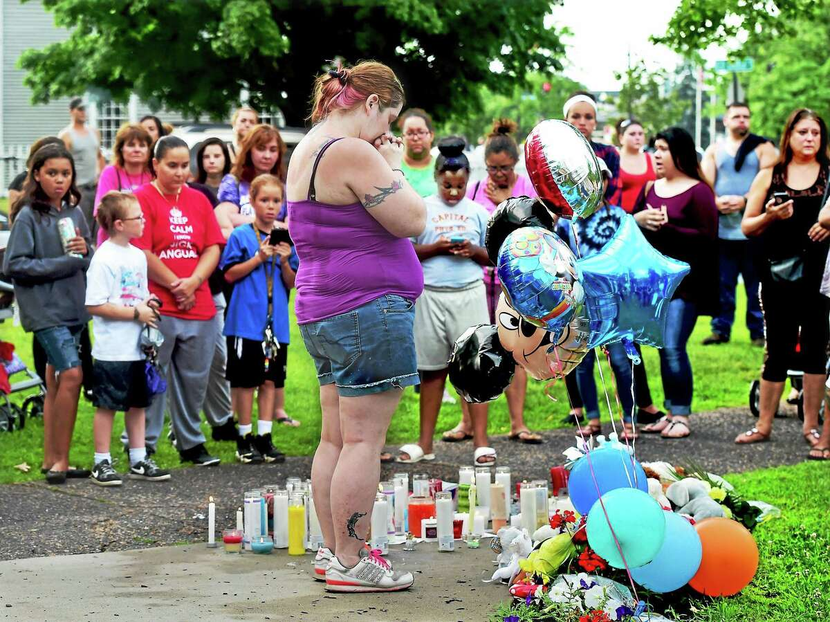 Middletown resident Carol Siecienski prays for 7-month-old baby Aaden Moreno at the South Green following a vigil July 7 at the South Congregational Church.