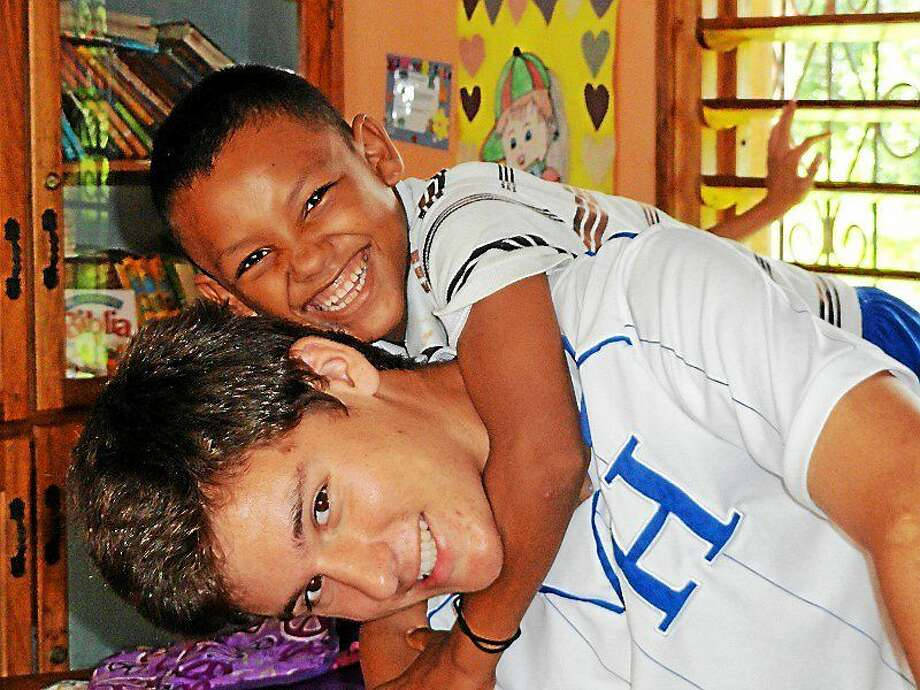 David Proctor, president of Honduras Children's Project, takes a break with one of his favorite students, Marvin, 9. (Contributed photo) Photo: Journal Register Co.