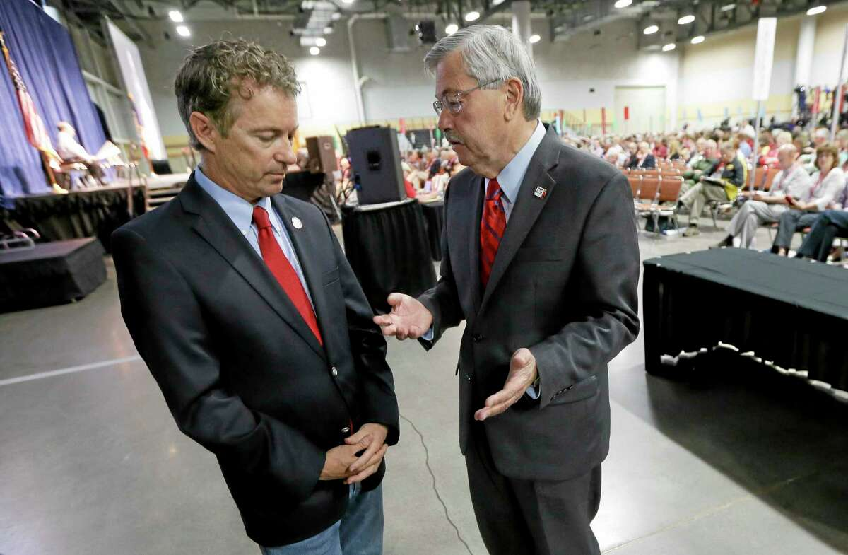 Iowa Gov. Terry Branstad, right, talks with Sen. Rand Paul, R-Ky., left, during the Iowa State Republican Convention, Saturday, June 14, 2014, in Des Moines, Iowa. (AP Photo/Charlie Neibergall)