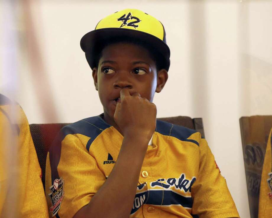 Jackie Robinson West Little League player DJ Butler listens as team attorney Victor Henderson addresses reporters at a news conference Wednesday in Chicago. Photo: Charles Rex Arbogast — The Associated Press  / AP