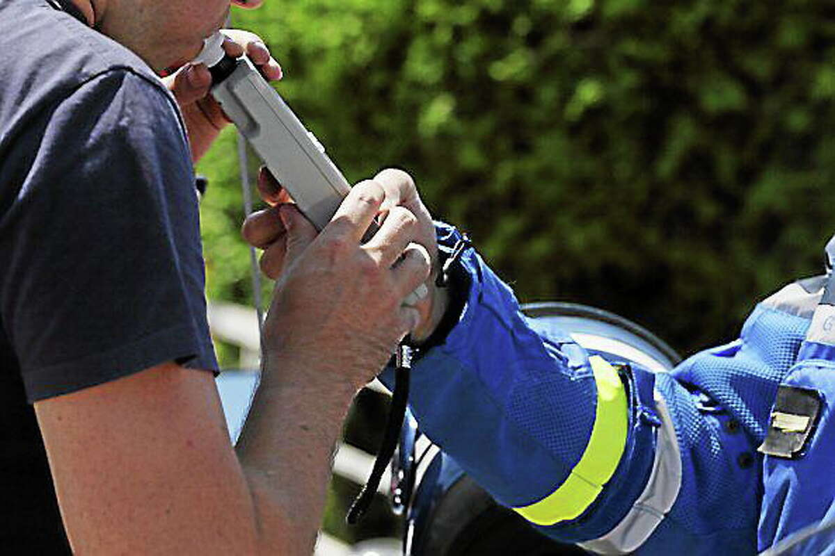 A French policeman uses an electronic breathalyzer on a driver arrested for speeding in July. Kenzo Tribouillard/AFP/Getty Images