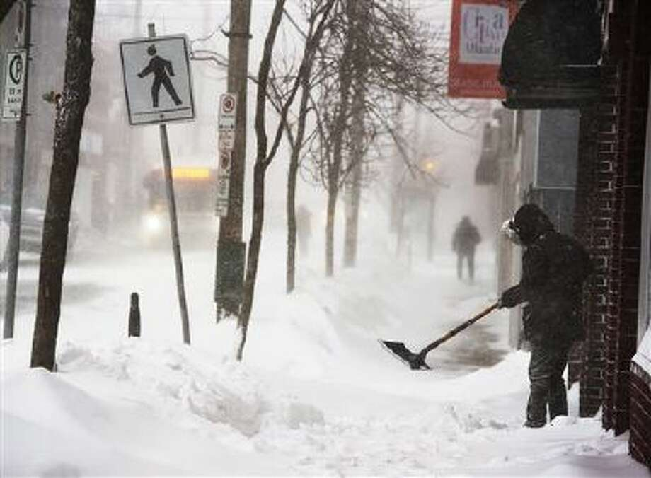A man clears a sidewalk Friday in blizzard conditions in Halifax, Nova Scotia. Photo: ASSOCIATED PRESS / AP2014