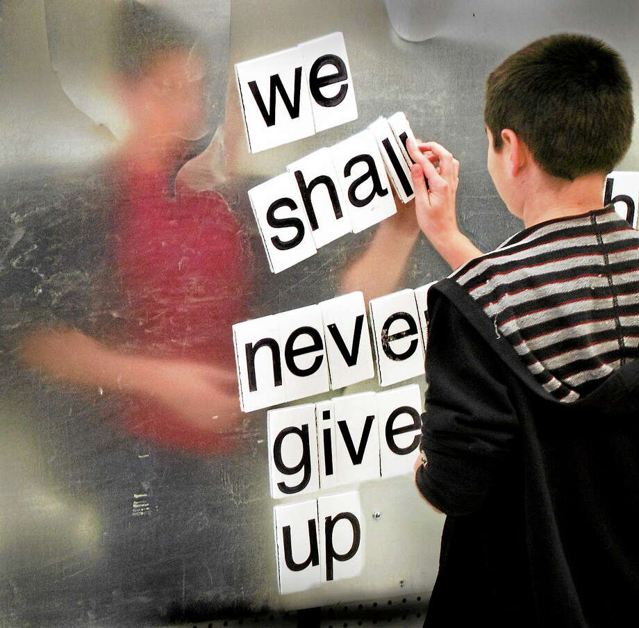 Newtown-Kyle Shelton, 10 of Newtown makes his contribution to the love here now poetry wall at the opening of the Newtown Healing Through The Arts Center.   Melanie Styengel/Register Photo: Journal Register Co.
