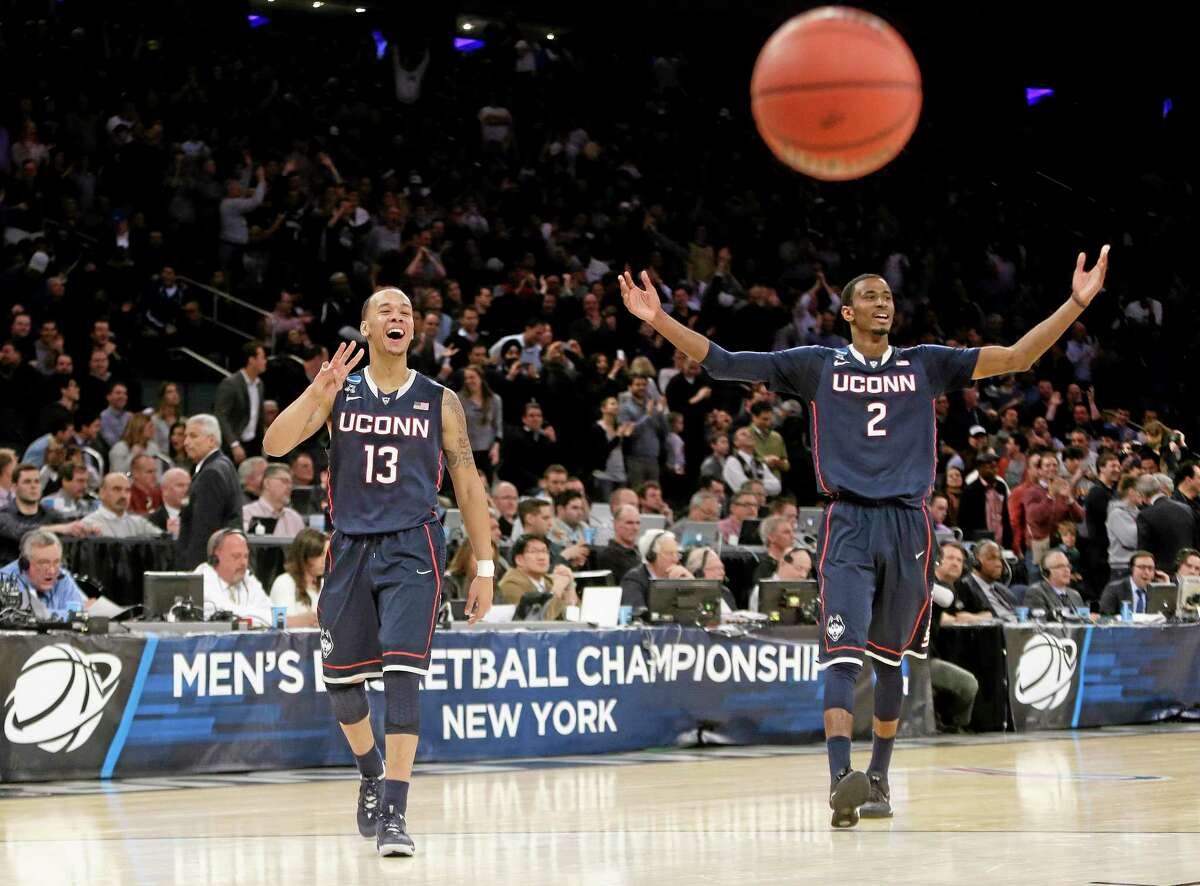 Connecticut's Shabazz Napier (13) and DeAndre Daniels (2) gesture to their teammates during the second half of a regional final against Michigan State in the NCAA college basketball tournament, Sunday, March 30, 2014, in New York. Connecticut won 60-54. (AP Photo/Frank Franklin II)
