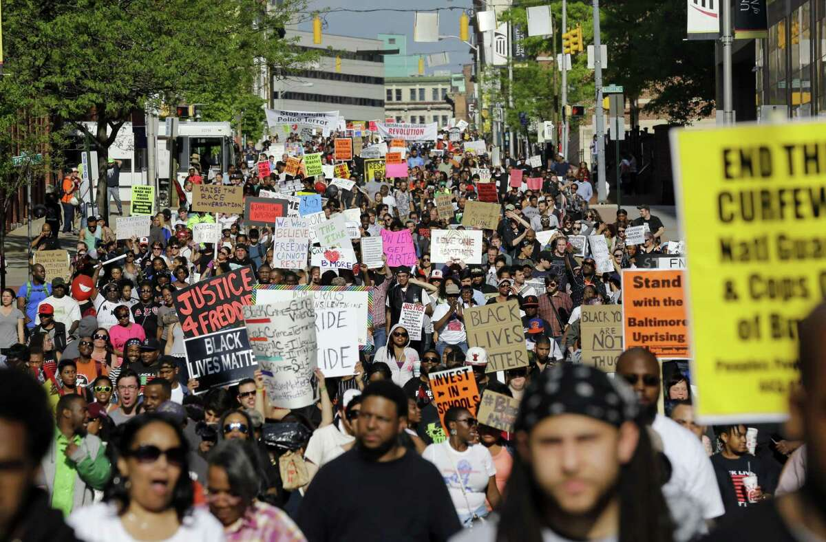 """FILE- In this May 2, 2015 file photo, protesters march through Baltimore the day after charges were announced against the police officers involved in Freddie Gray's death. A medical examiner found Freddie Gray suffered a """"high-energy injury,"""" most likely caused when the Baltimore police van he was riding in braked sharply, according to an autopsy report obtained by The Baltimore Sun. (AP Photo/Patrick Semansky, File)"""