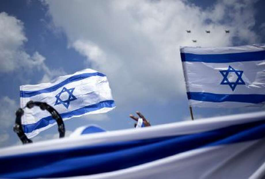 An African migrant worker holds Israeli flags during Independence Day in Tel Aviv, Tuesday, April 16, 2013.