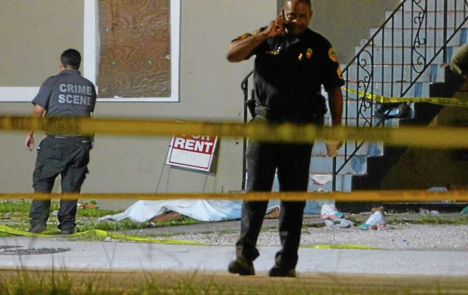Authorities work the scene where at least two people were killed and multiple others wounded following a shooting early Tuesday, June 24, 2014, in Miami's Liberty City neighborhood. Miami City Manager Daniel Alfonso said the dead include a 20-year-old man and a teenage girl. (AP Photo/The Miami Herald, Walter Michot) Photo: AP / The Miami Herald