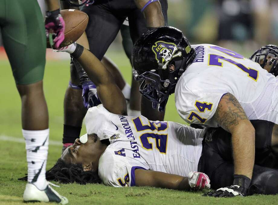 East Carolina running back Breon Allen (25) holds up the football after scoring a touchdown against South Florida on Oct. 11 in Tampa, Fla. Looking on is offensive lineman Taylor Hudson (74). Photo: Chris O'Meara — The Associated Press  / AP