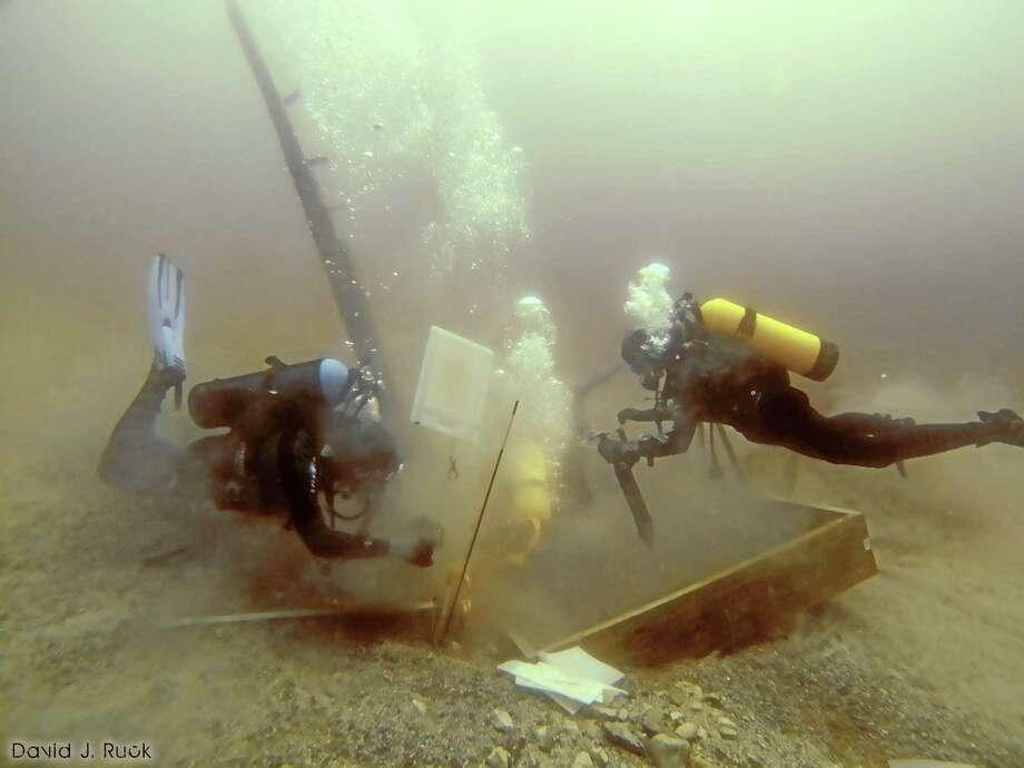 FILE - In this June 16, 2013 photo provided by Great Lakes Exploration Group,  divers inspect a hole being dug beside a wooden beam jutting from the floor of Lake Michigan during  exploration for the 17th century ship the Griffin. A debris field at the bottom of Lake Michigan may be the remains of the long-lost Griffin, a vessel commanded by a 17th-century French explorer, said a shipwreck hunter who has sought the wreckage for decades. Steve Libert told The Associated Press that his crew found the debris this month about 120 feet from the spot where they removed a wooden slab a year ago that was protruding from the lake bottom. (AP Photo/Great Lakes Exploration Group, David J. Ruck, File) Photo: AP / Great Lakes Exploration Group