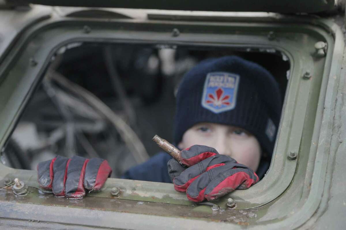 A boy looks at a bullet casing that he has found in a Russia-made trophy APC seized by the Ukrainian troops in Ukraine's east at an open-air exhibition in front of the golden-domed St Michael Cathedral in Kiev, Ukraine, Saturday, Feb. 21, 2015. Russian-made military trophies seized or destroyed by the Ukrainian troops were exhibited in the Ukrainian capital as an evidence of Russia's military presence in Ukraine's east, the fact that Russia have still denied, Ukrainian officials said. (AP Photo/Efrem Lukatsky)