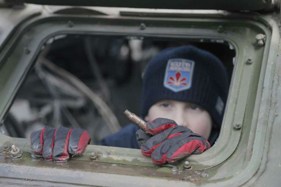 A boy looks at a bullet casing that he has found in a Russia-made trophy APC seized by the Ukrainian troops in Ukraine's east at an open-air exhibition in front of the golden-domed St Michael Cathedral in Kiev, Ukraine, Saturday, Feb. 21, 2015. Russian-made military trophies seized or destroyed by the Ukrainian troops were exhibited in the Ukrainian capital as an evidence of Russia's military presence in Ukraine's east, the fact that Russia have still denied, Ukrainian officials said. (AP Photo/Efrem Lukatsky) Photo: AP / AP