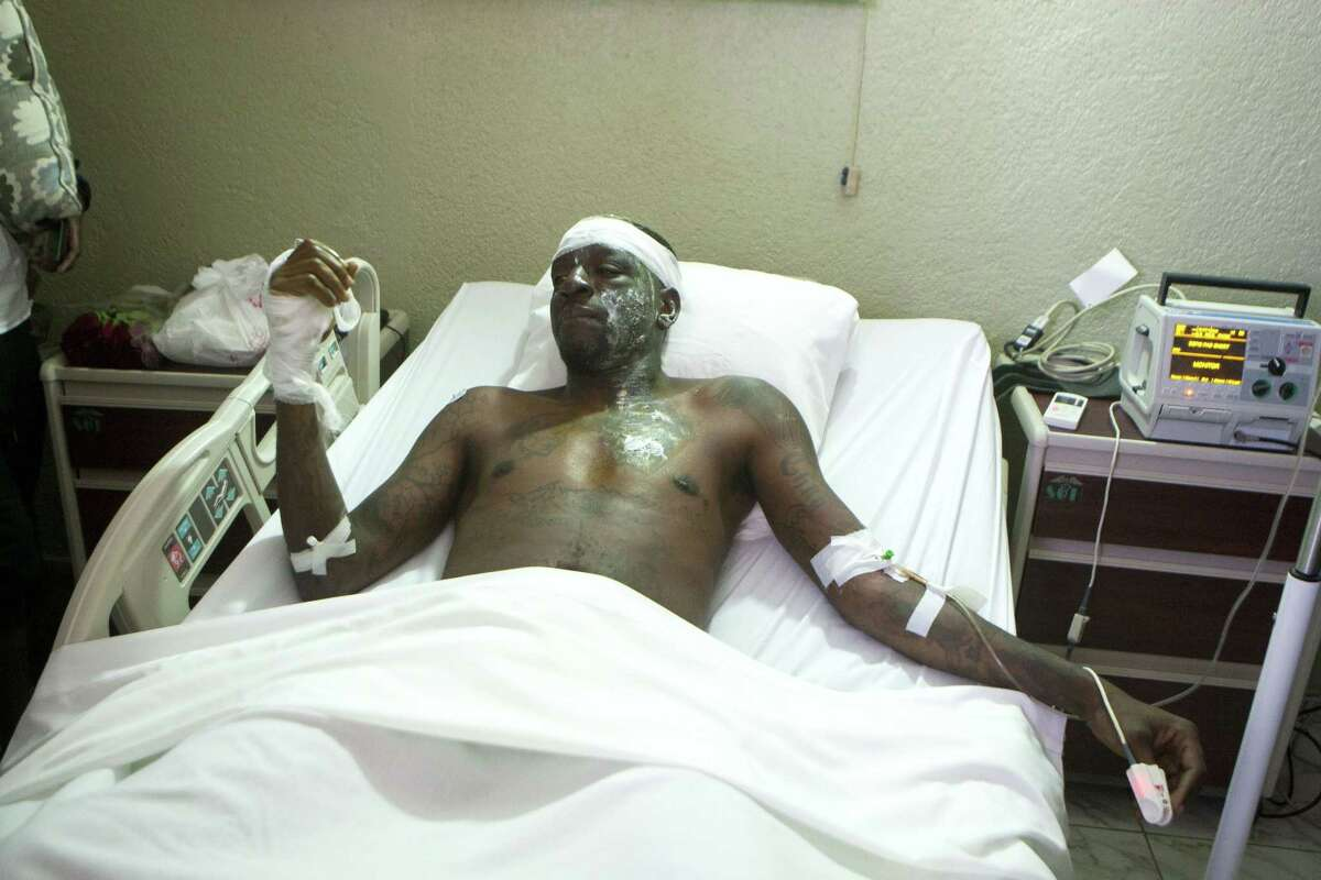"""Singer Daniel Darinus, whose stage name is """"Fantom,"""" from the Barikad Crew music group, talks with journalists from his hospital bed in Port-au-Prince, Haiti, Wednesday, Feb. 18, 2015. Daniel is recovering after being shocked by high-voltage wires during Tuesday's Carnival parade. (AP Photo/Dieu Nalio Chery)"""
